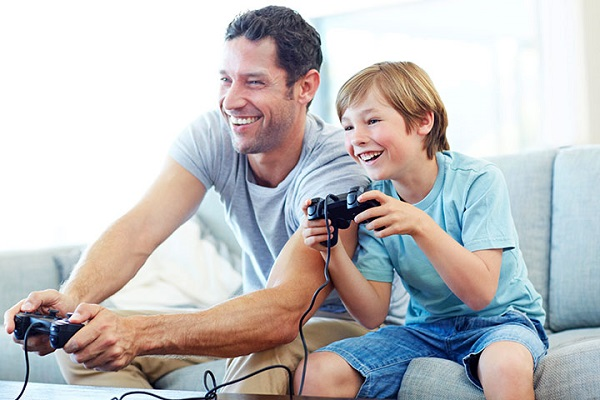 Image of Happy Son and Father Holding Joystick and Having Fun while playing games.